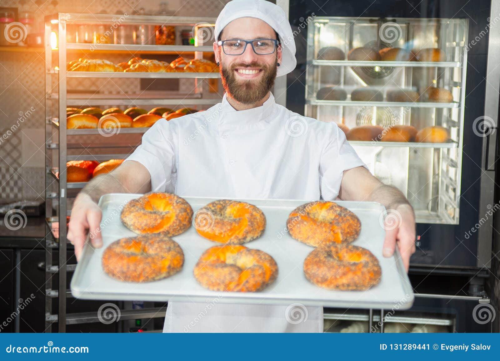 Een jonge knappe bakker die verse ongezuurde broodjes met papaverzaden houden op een dienblad op de achtergrond van een oven en e