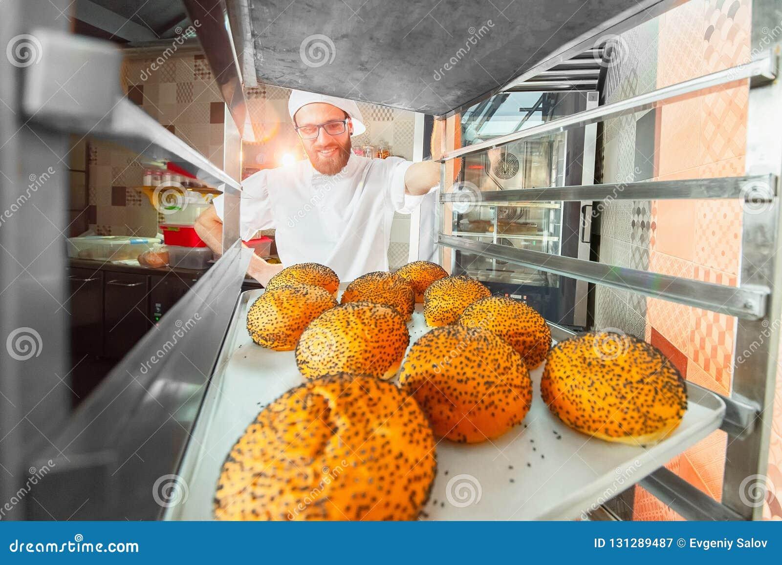 Een jonge knappe bakker neemt verse hete broodjes met papaverzaden van de oven voor de bakkerij