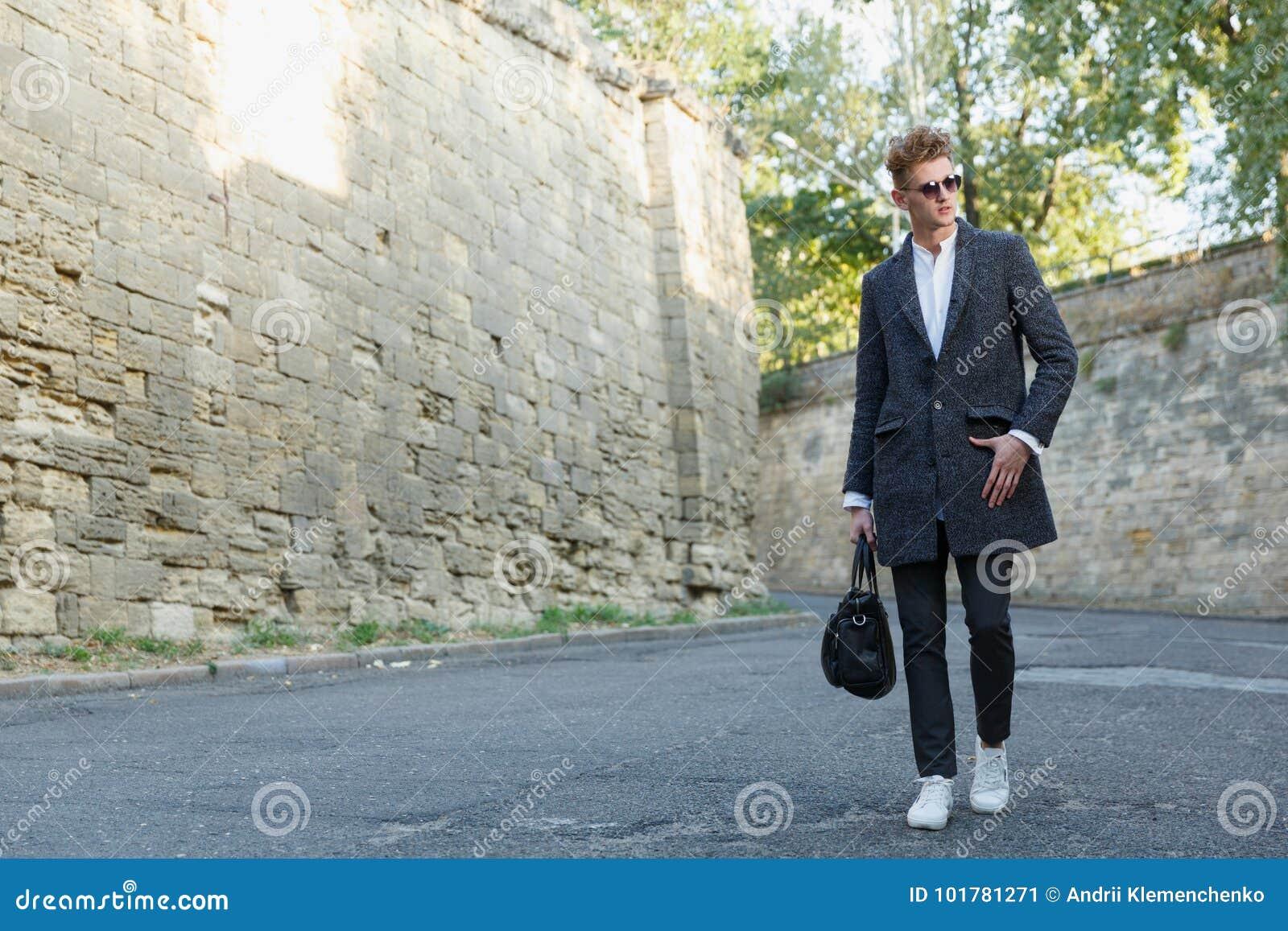 Een jonge, lange, professionele zakenman loopt onderaan de straat in een laag met een klassieke aktentas