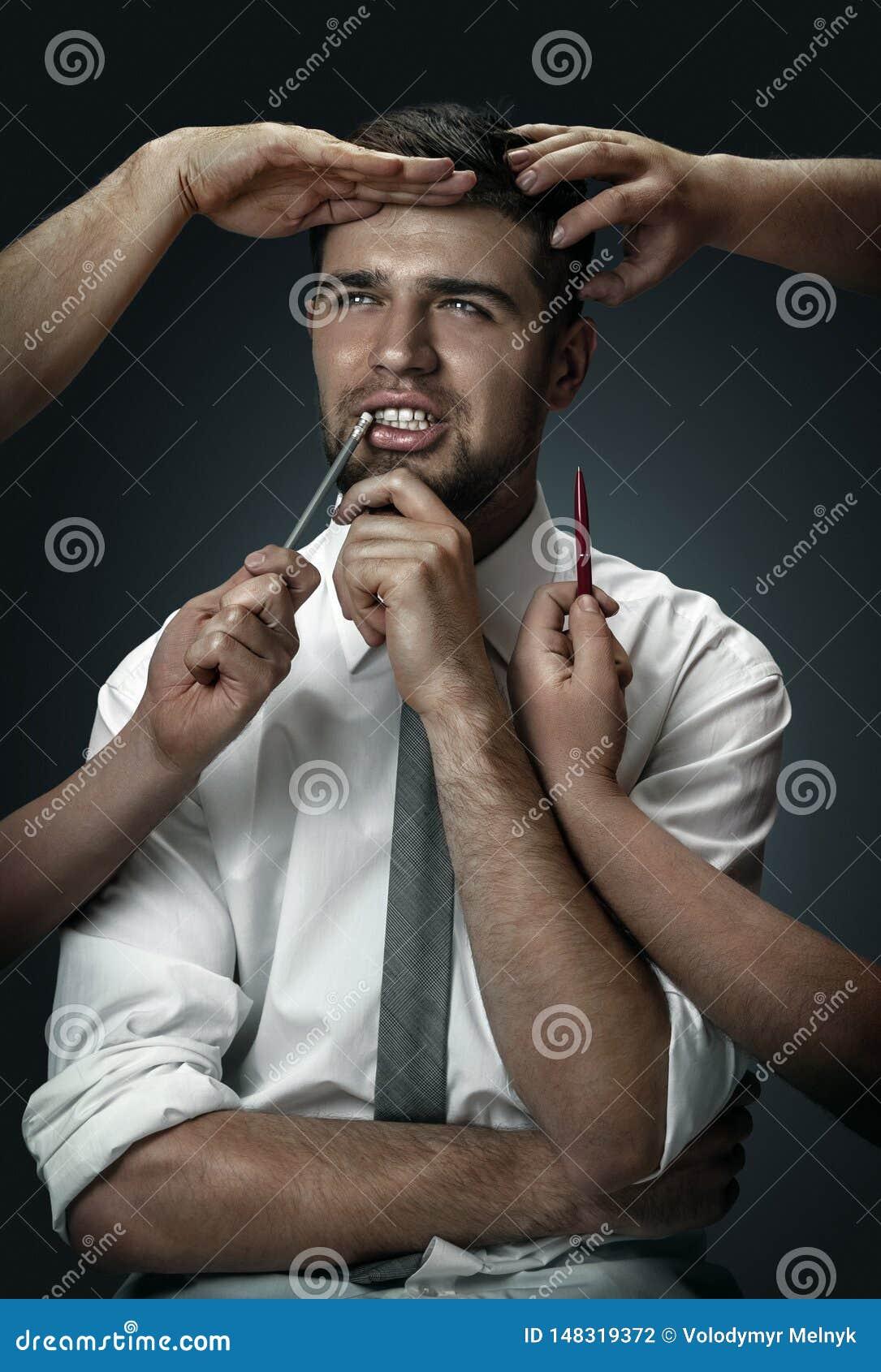 Een jonge mens die door handen zoals zijn eigen gedachten wordt omringd