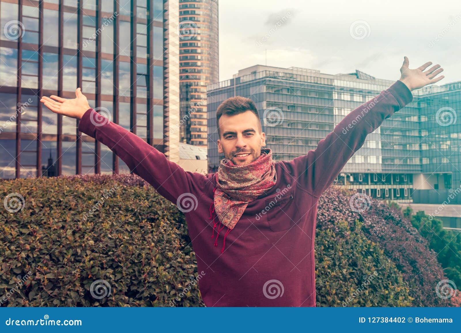 Een jonge mens die zijn wapens, open palmen in het moderne gelukkige stadscentrum -, succes en voltooiingsconcepten opheffen