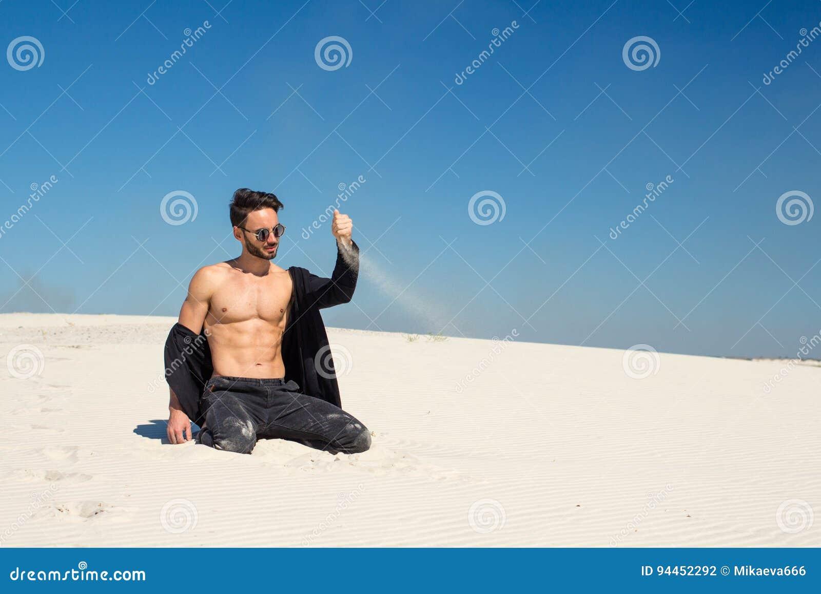 Een jonge mens giet prachtig zand met één hand