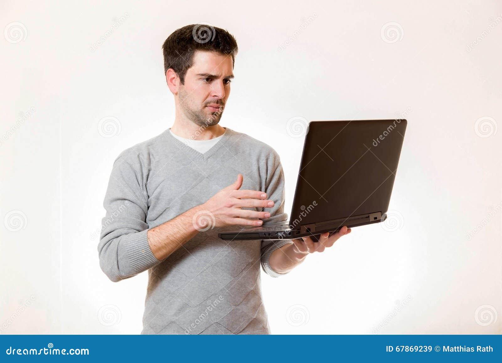 Een jonge mens kijkt wantrouwend op zijn laptop