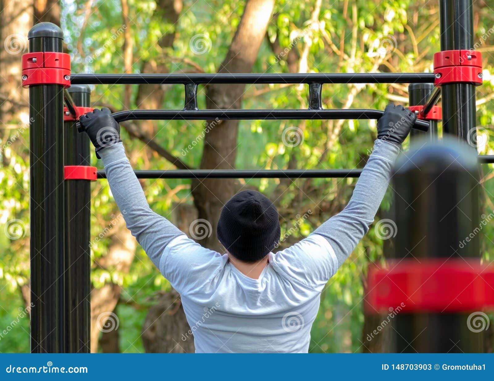 Een jonge mens voert een sportenoefening uit trekkend op de simulatordwarsbalk De openlucht opleiding ontwikkelt de sterkte van d