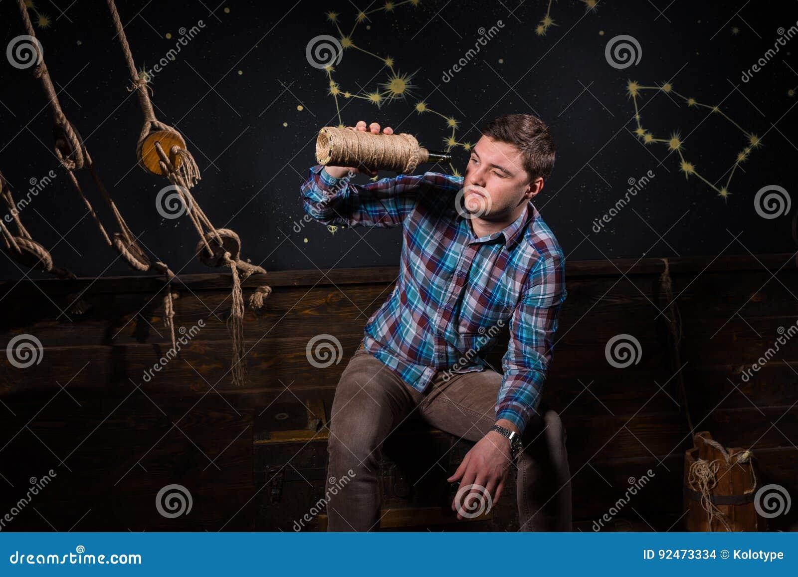 Een jonge mens zit op een borst, onderzoekend glasfles en tryin