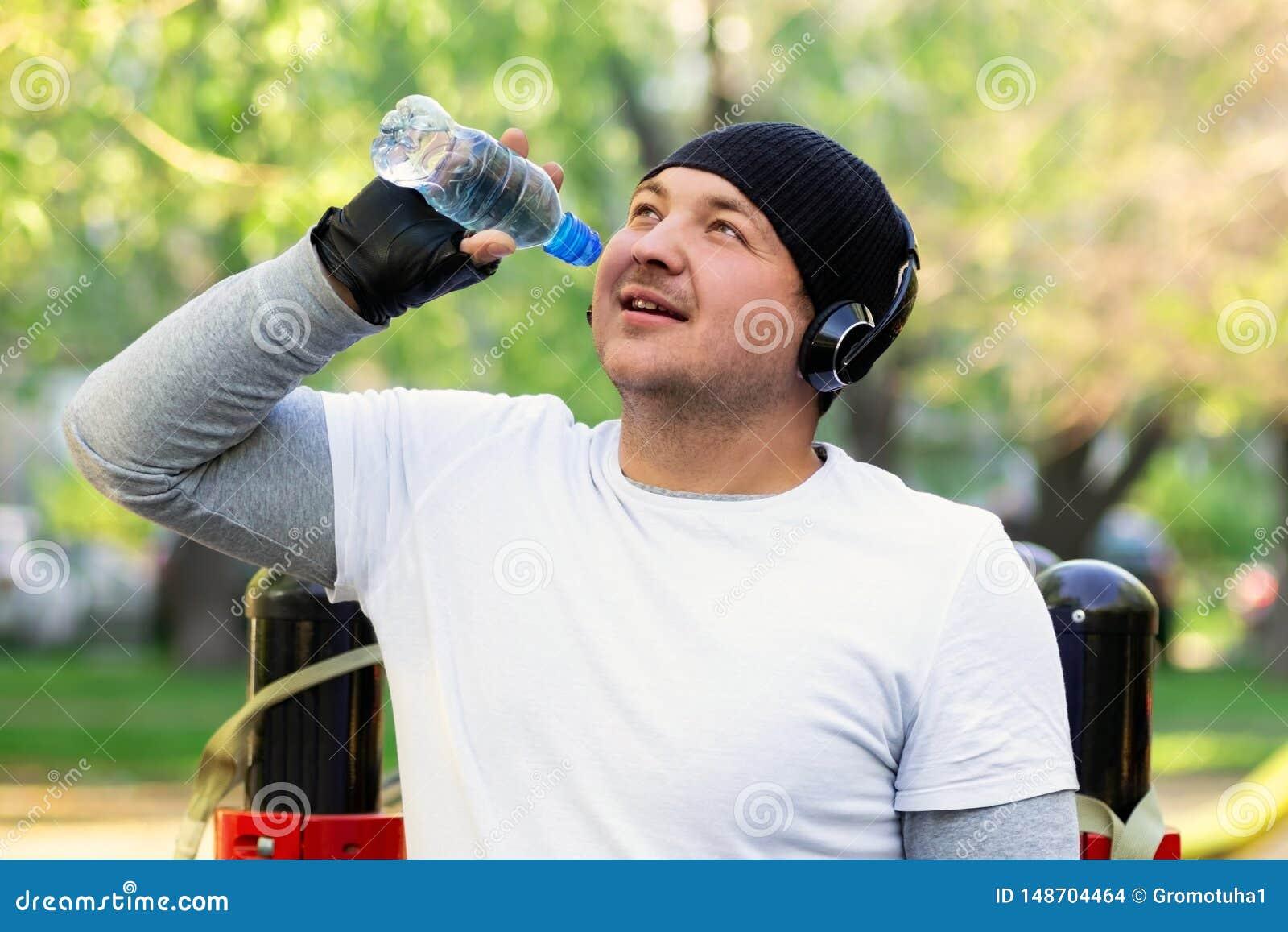Een jonge mensenatleet met hoofdtelefoons op zijn hoofd drinkwater na een harde training op de straat Kerelglimlachen die genoege