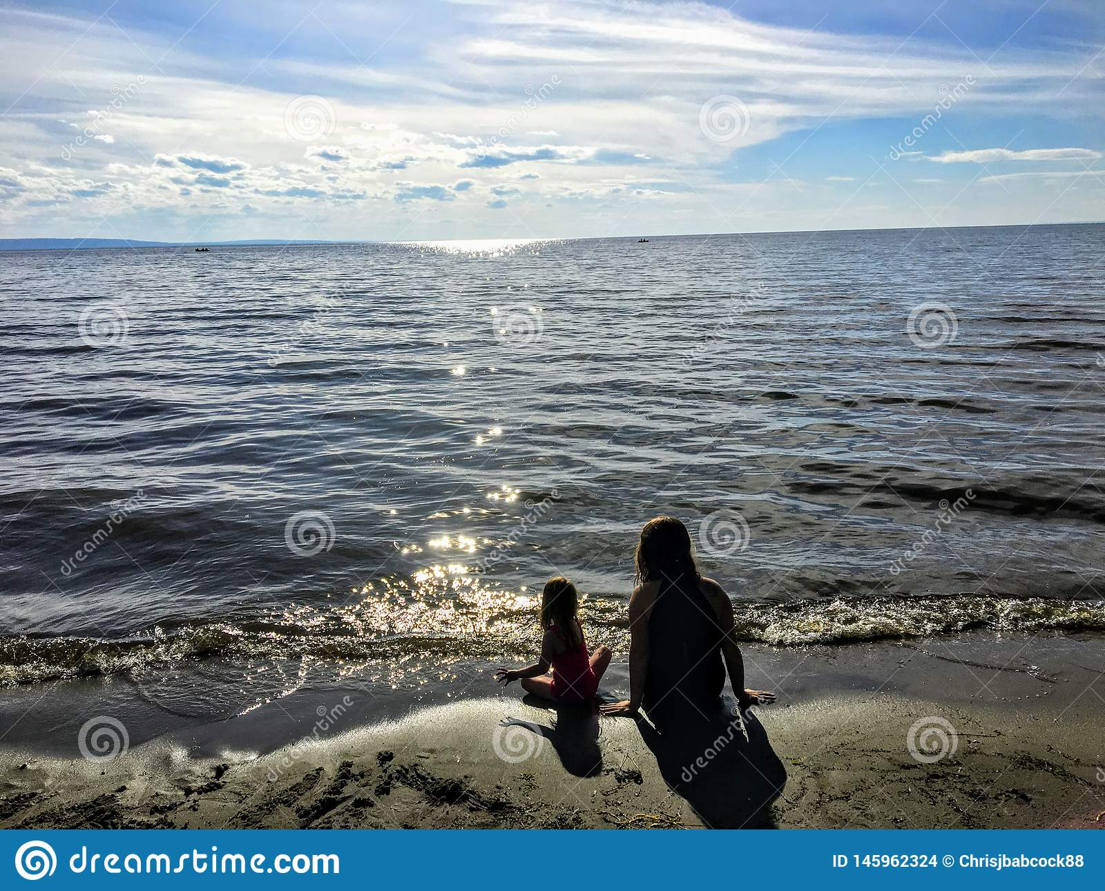Een jonge moeder en haar zitting van de peuterdochter samen alleen op een zandig strand die op het fonkelende meerwater letten