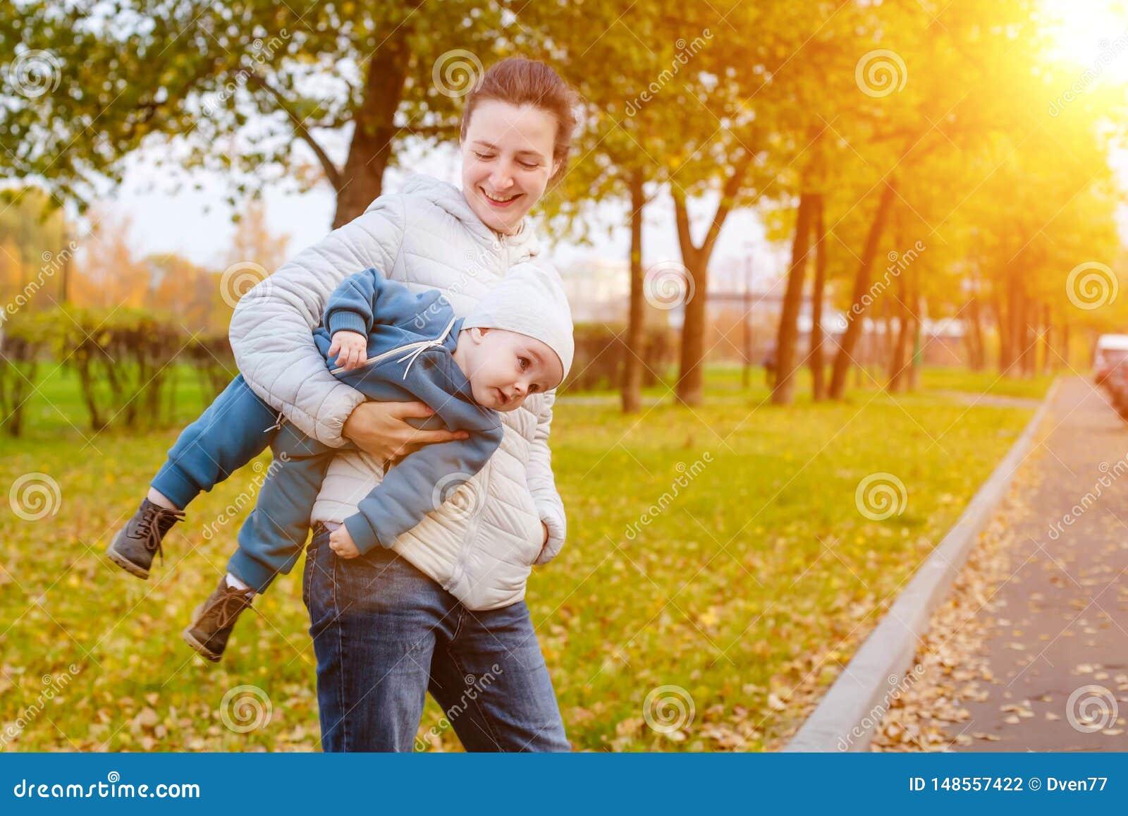 Een jonge moeder vervoert een één éénjarigejongen in haar wapens Gang met het kind in het park bij zonnige dag