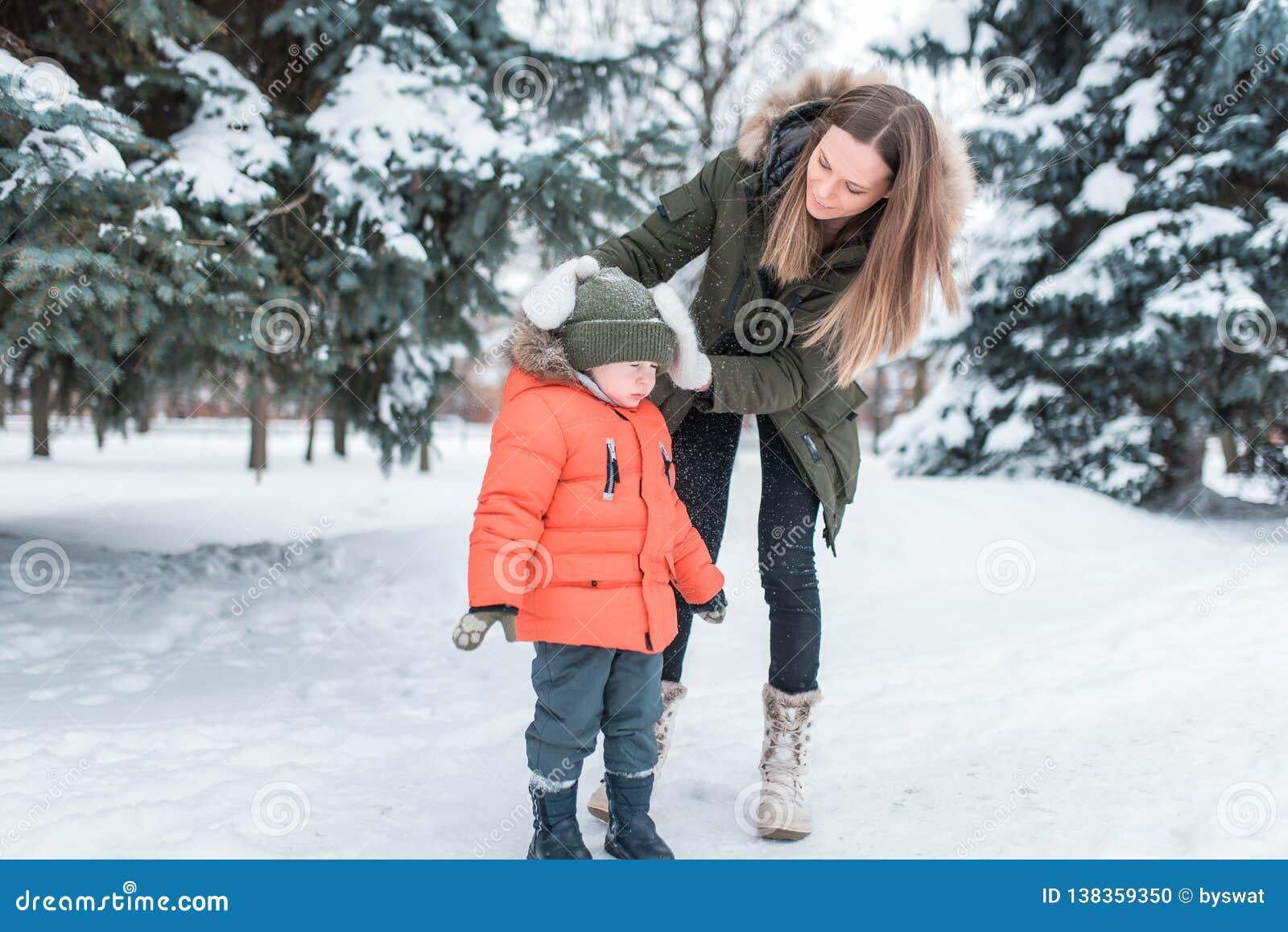 Een jonge moeder, een vrouw schudt van de sneeuw van een jongen 4-6 jaar oude zoon In de winter in het park buiten Het geven voor