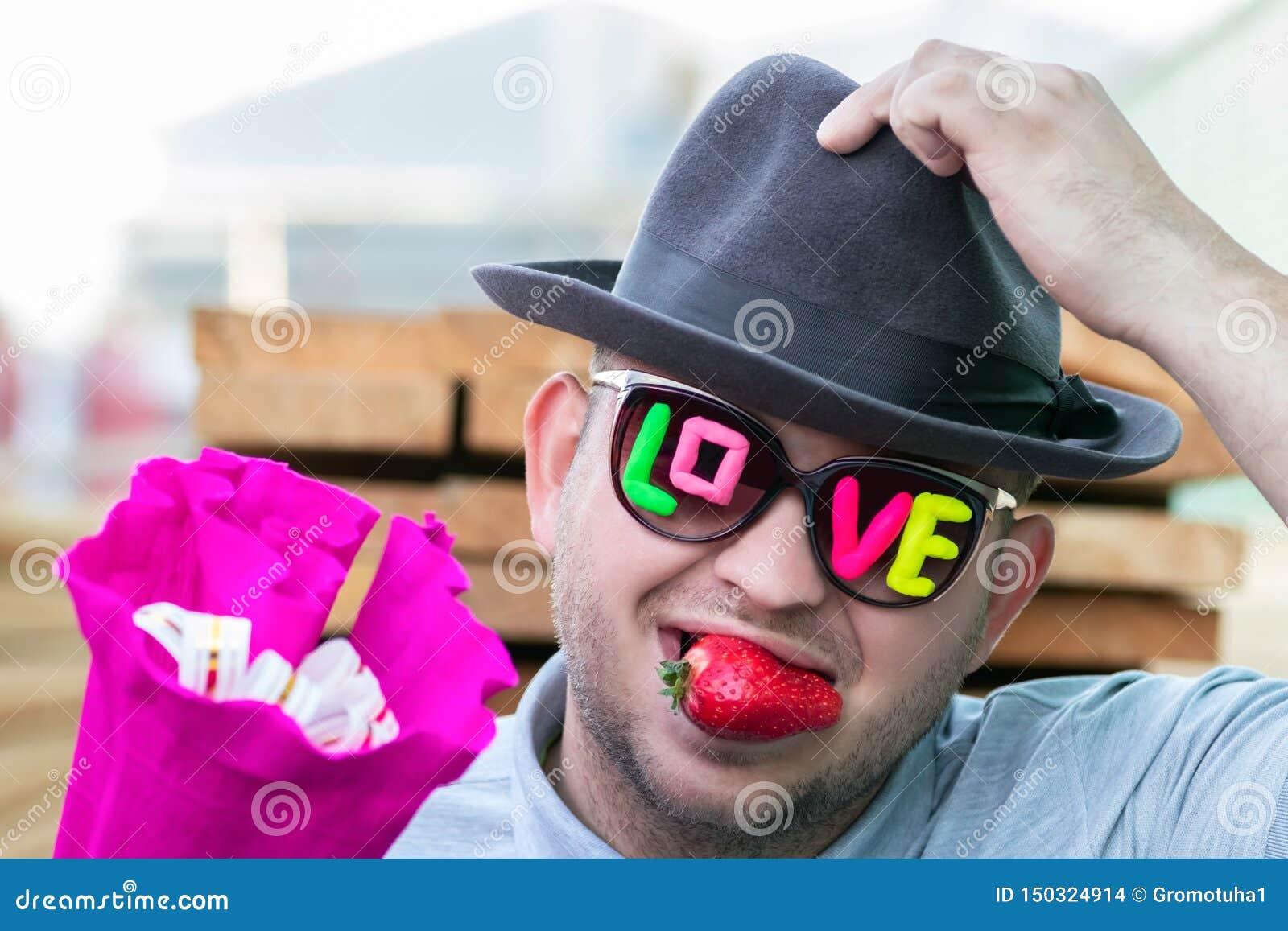 Een jonge, romantische, het glimlachen kerel in donkere glazen met de van de inschrijvingsliefde en bes aardbeien in zijn mond ge
