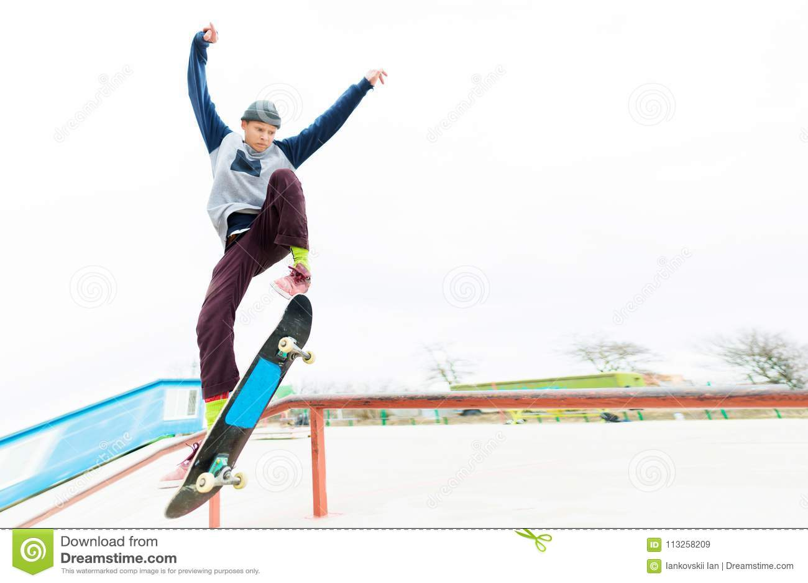 Een jonge tiener, een skateboarder, doet een truc op het traliewerk in een skatepark Het concept de jeugdsporten in stedelijk