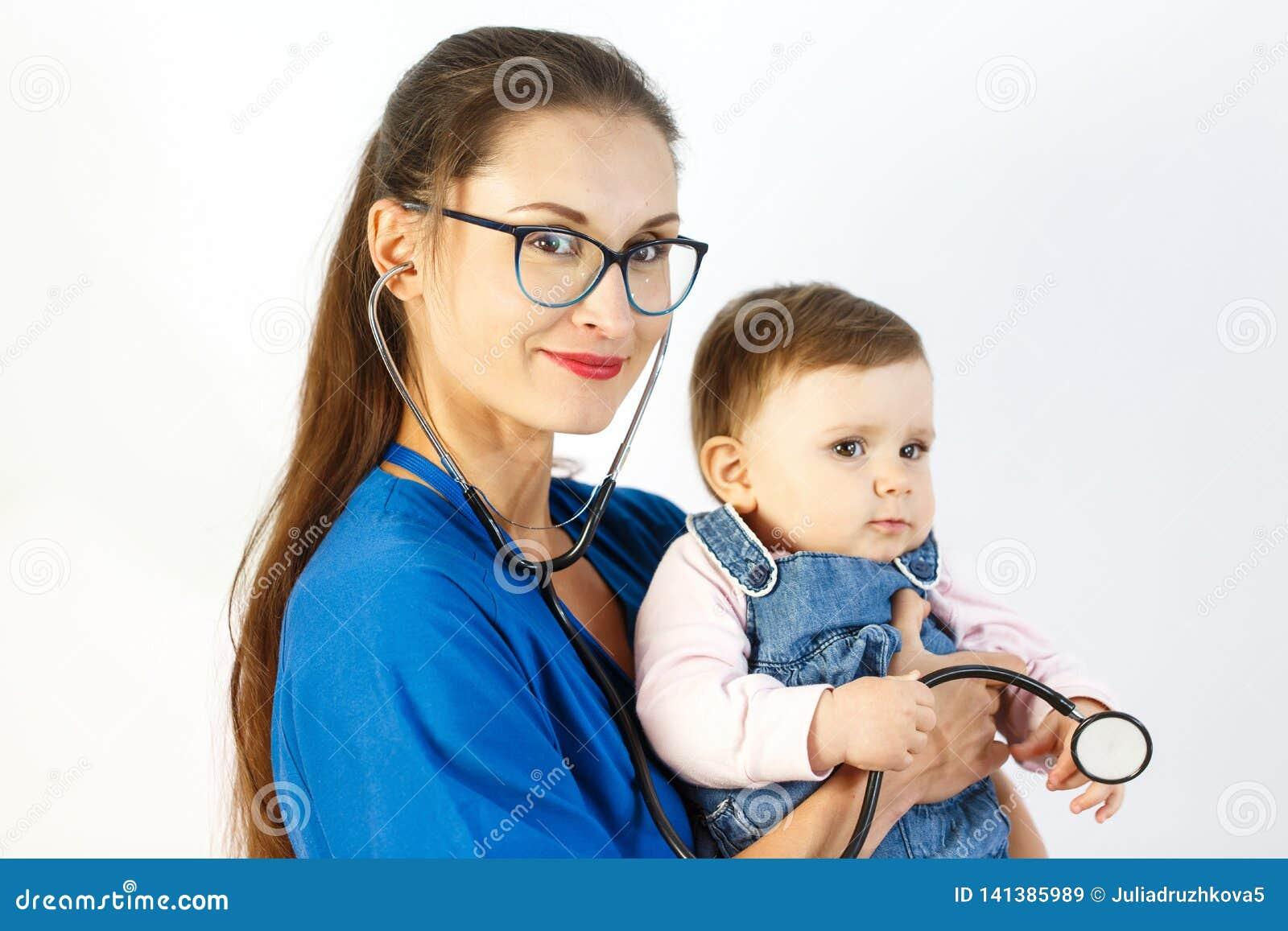 Een jonge vrouw arts houdt een baby in haar wapens, glimlacht zij, en een kind speelt met een stethoscoop