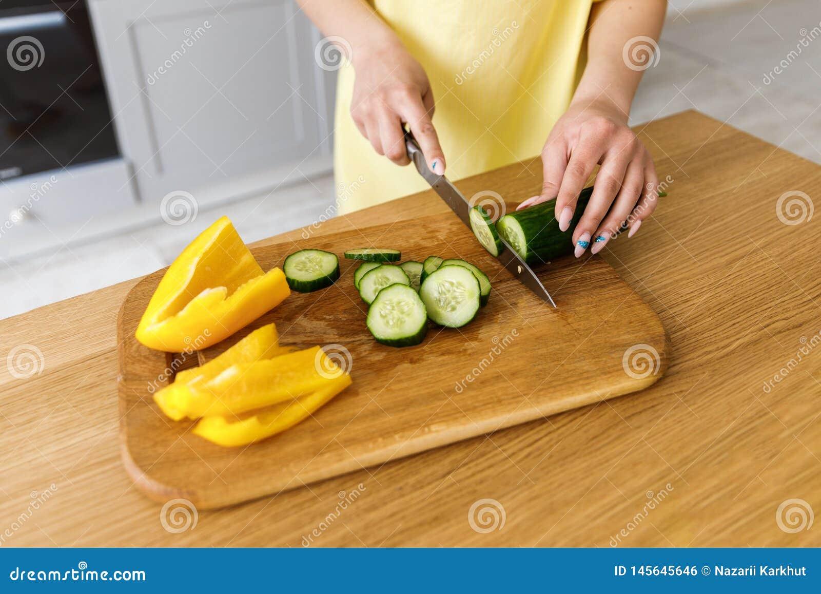 Een jonge vrouw die verse groenten op een houten raad voor salade snijden cooking Het meisje snijdt een komkommer, close-up