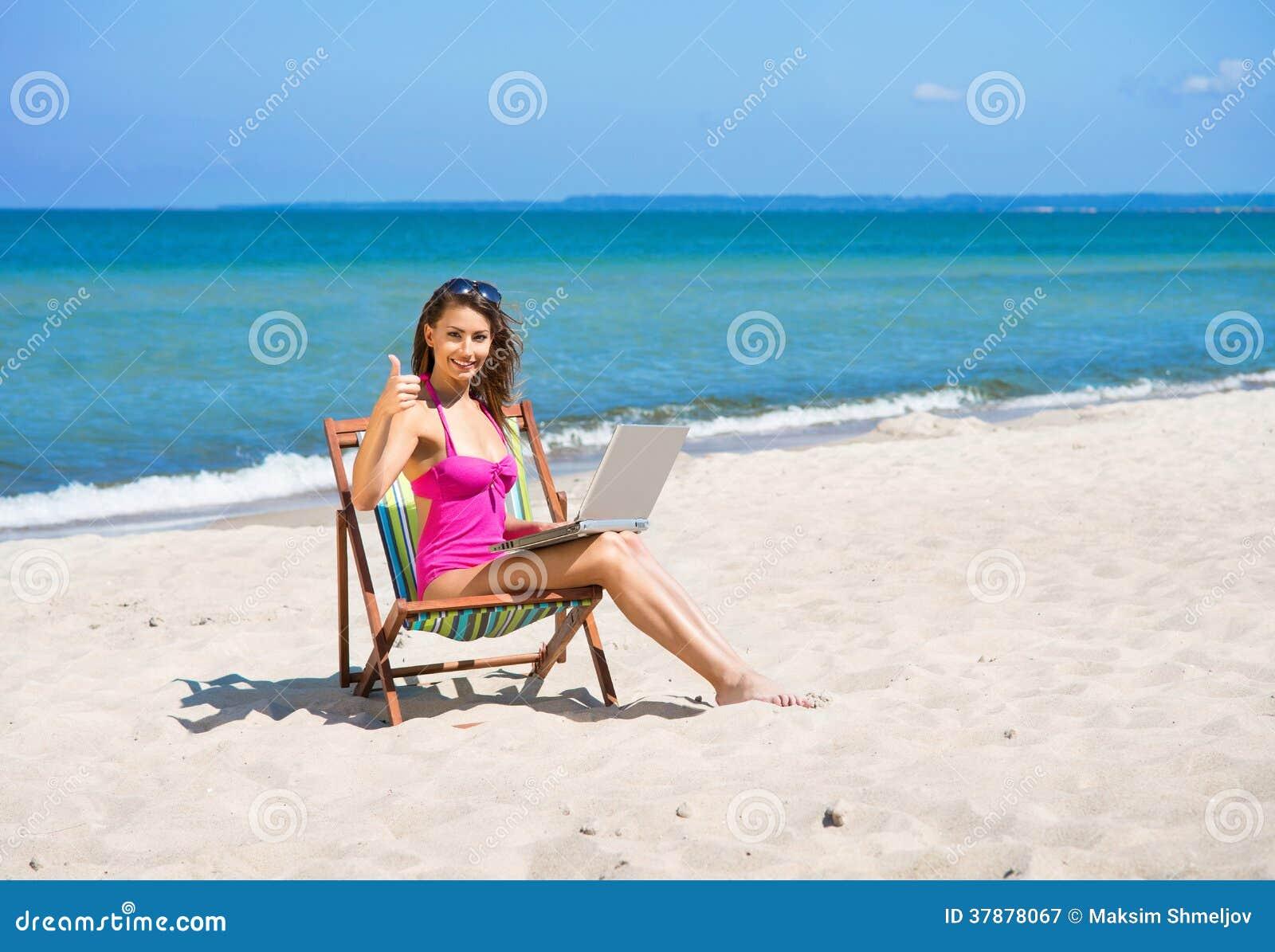 Een jonge vrouw in een zwempak en met laptop op het strand