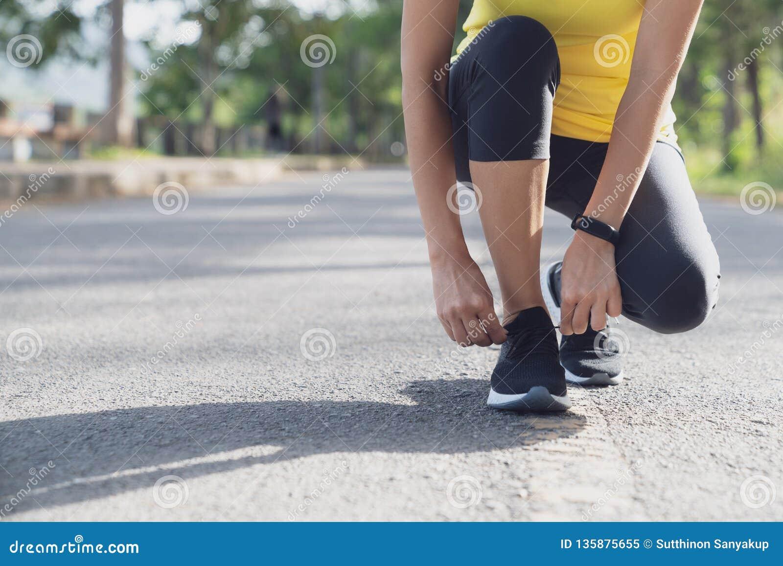 Een jonge vrouw hield op om een koord te binden terwijl het lopen in het stadion, de agent bindende schoenveter van de Geschikthe