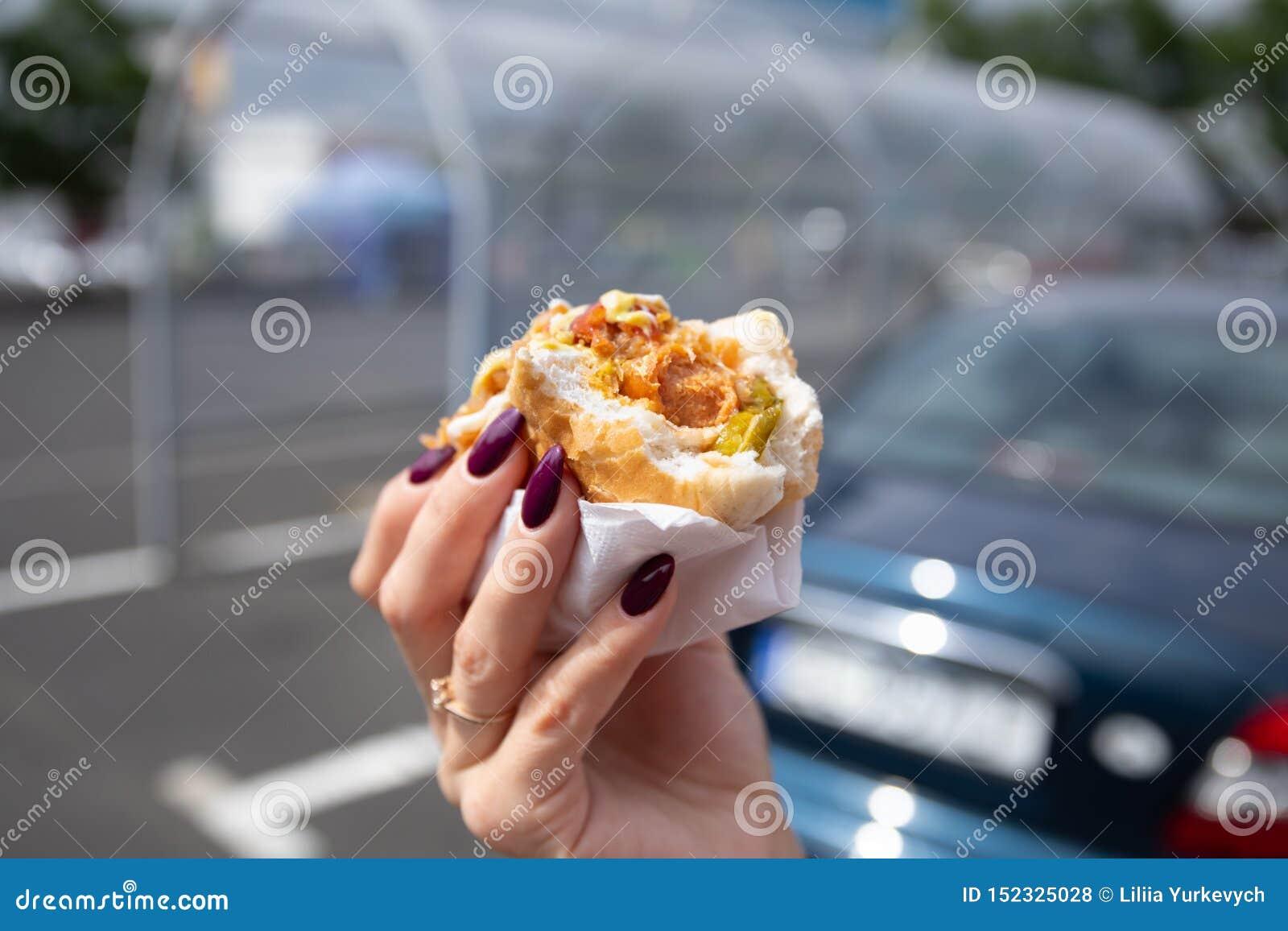 Een jonge vrouw houdt een gebeten hotdog