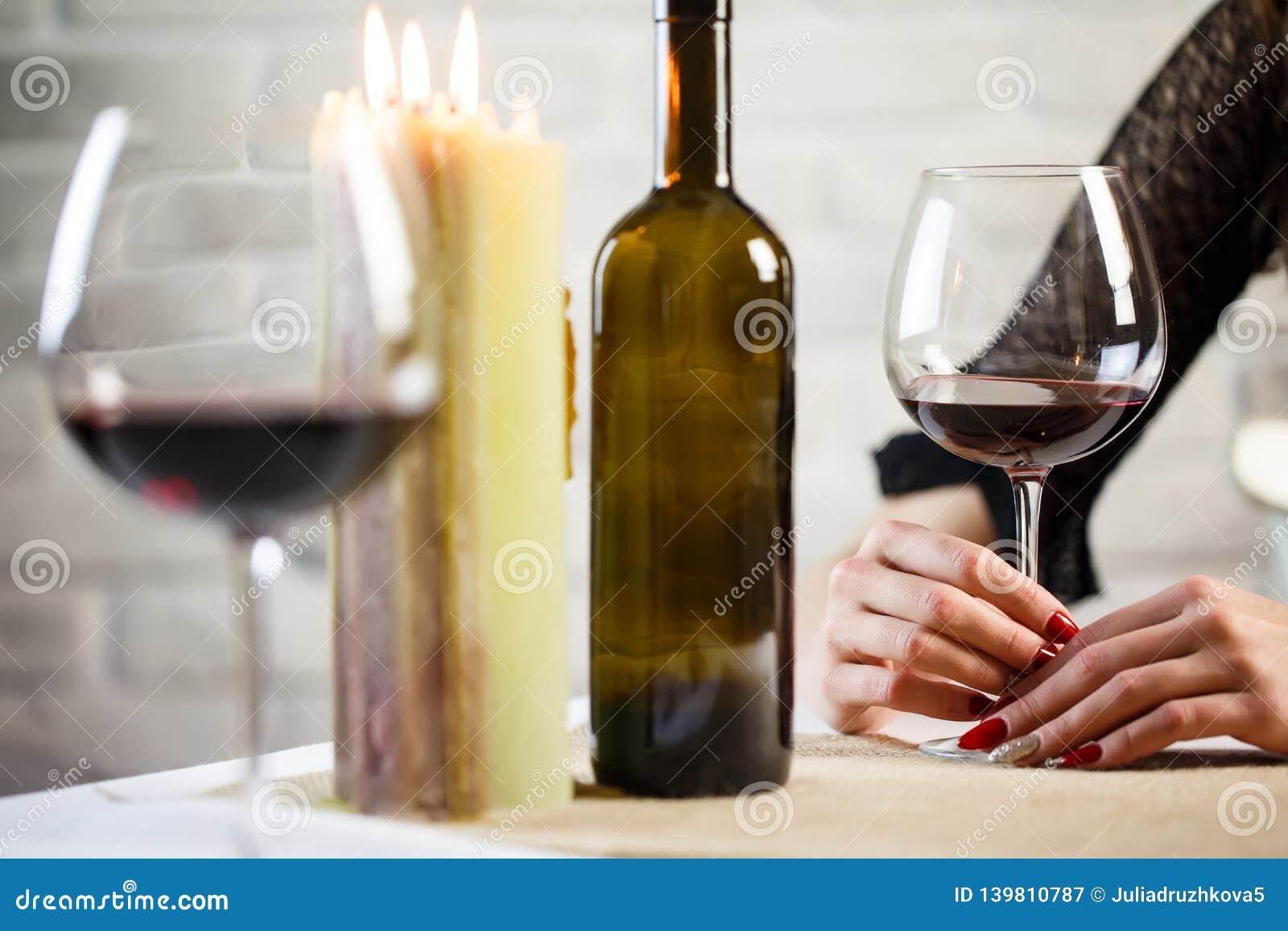 Een jonge vrouw houdt in haar hand een glas wijn op een afspraak tussen onbekende man en vrouw Wijnglas twee op de lijst Sluit om