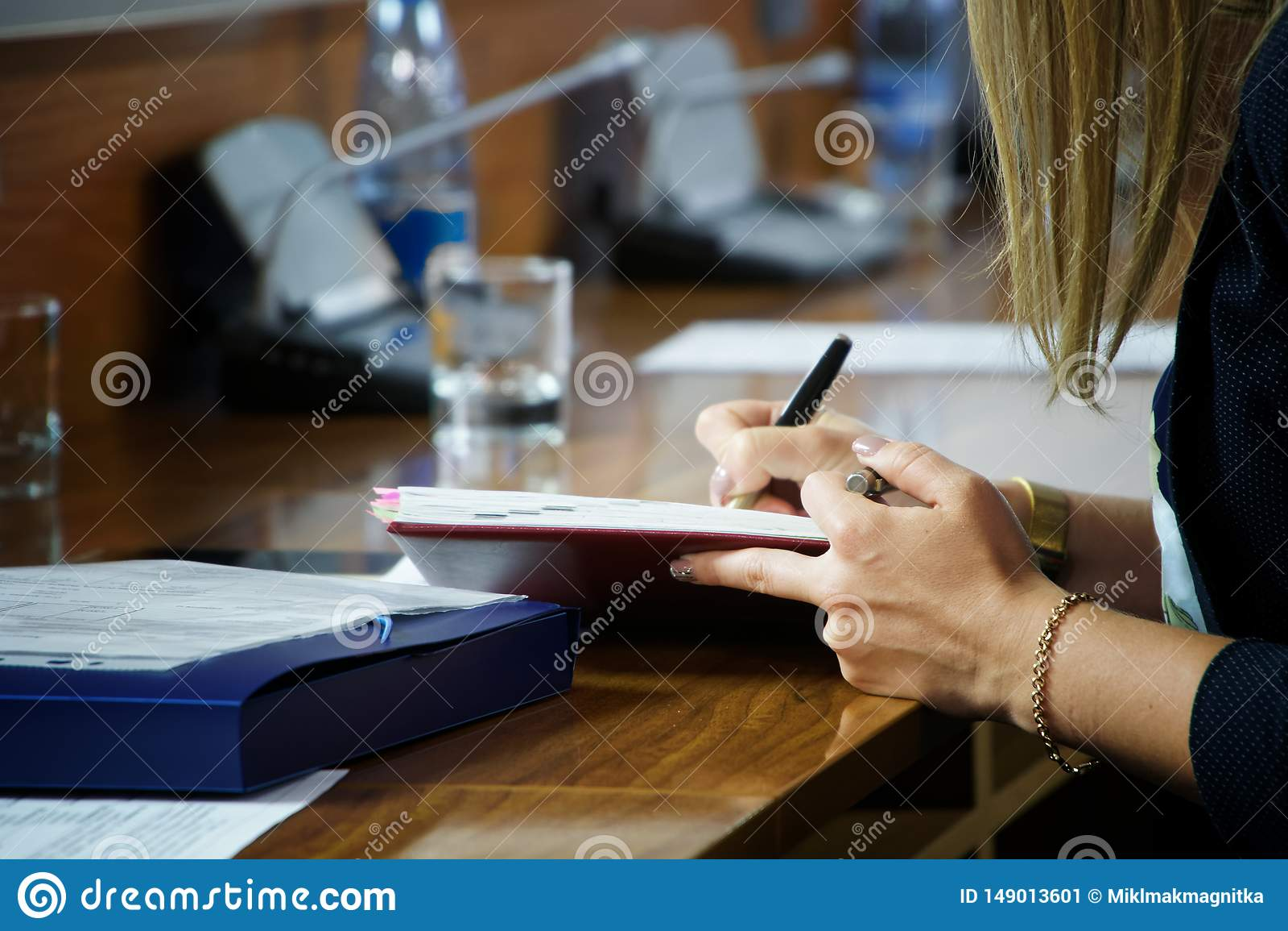 Een jonge vrouw met een gouden armband schrijft nota s in een dik notitieboekje Verslag in de organisator