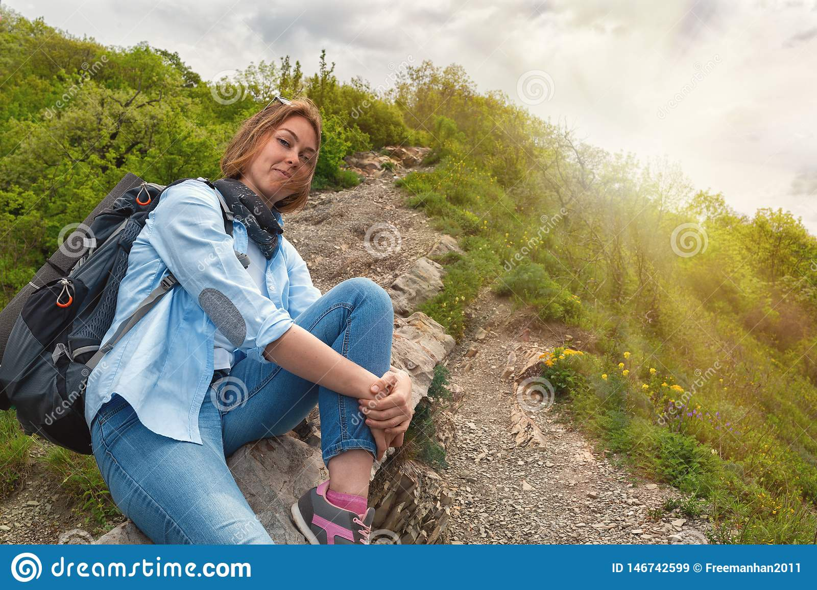Een jonge Vrouwenzitting op een weg van de bergsteen en het stellen voor de camera Achtergronden: zon licht Knippend inbegrepen w