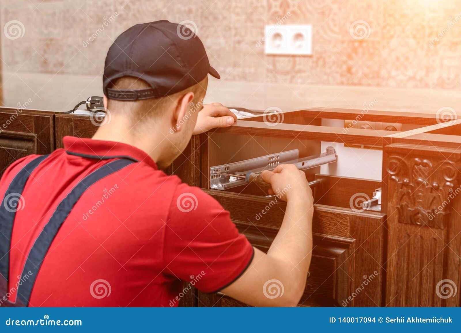 Een jonge werknemer installeert een lade Installatie van modern houten keukenmeubilair