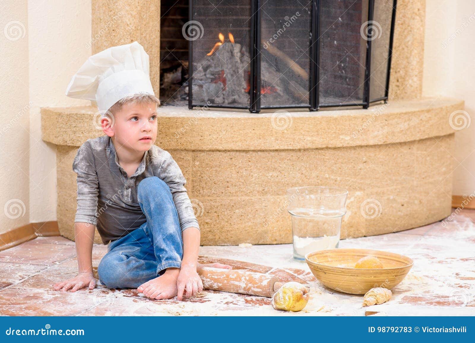 Een jongen in chef-kok` s hoeden dichtbij de open haardzitting op de keukenvloer met bloem wordt bevuild, spelend met voedsel, di