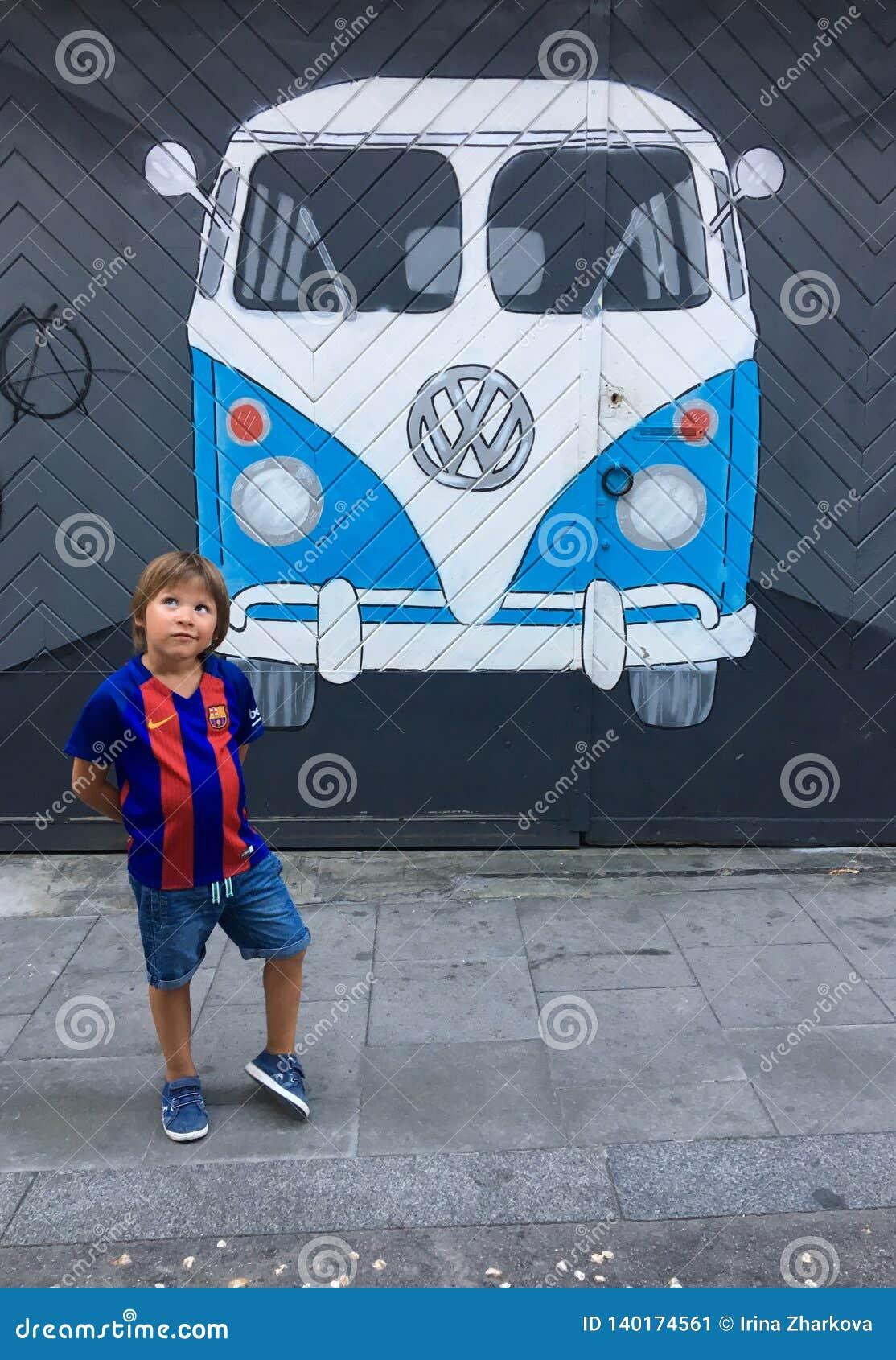 Een jongen in de vorm van Barcelona FC dichtbij graffiti het schilderen van een Volkswagen-bus op een muur wordt geschilderd die