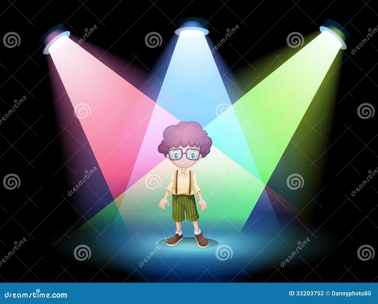 Een jongen die een oogglas dragen die zich op het stadium met schijnwerpers bevinden