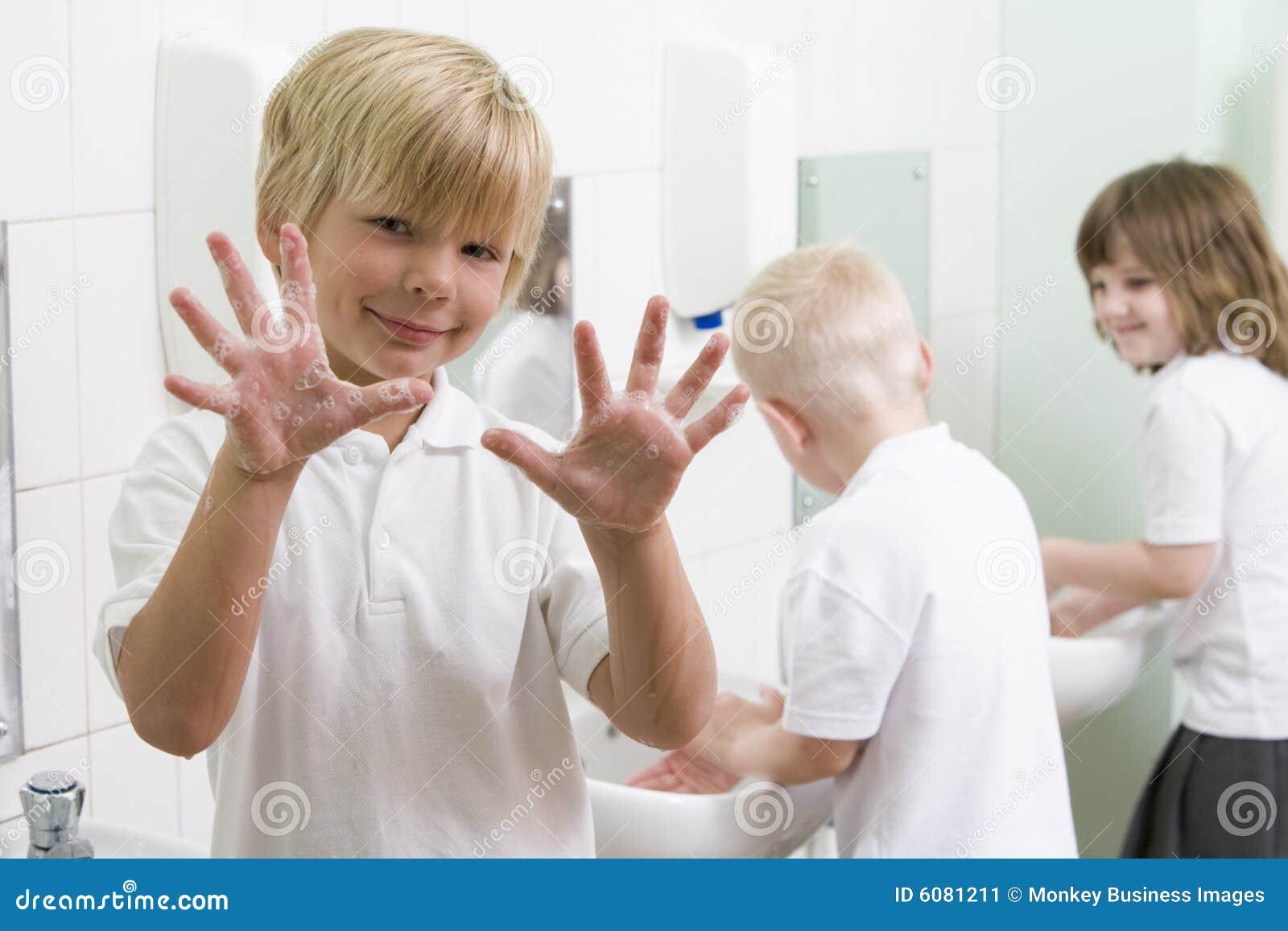 Een jongen die van hem toont dient een schoolbadkamers in