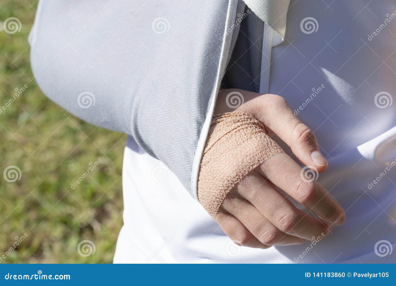 Een jongen met verwond dient een het bevestigen verband op de achtergrond van een voetbalgebied in
