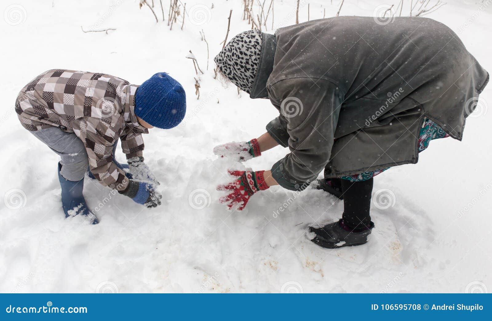 Een jongen met zijn grootmoeder die in de sneeuw spelen