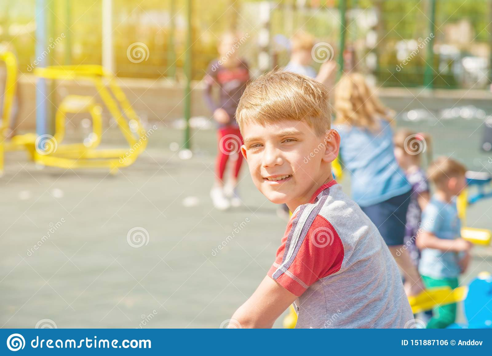 Een jongen op de speelplaats, een portret van een kind tegen de achtergrond van de schommeling van kinderen en vermaak