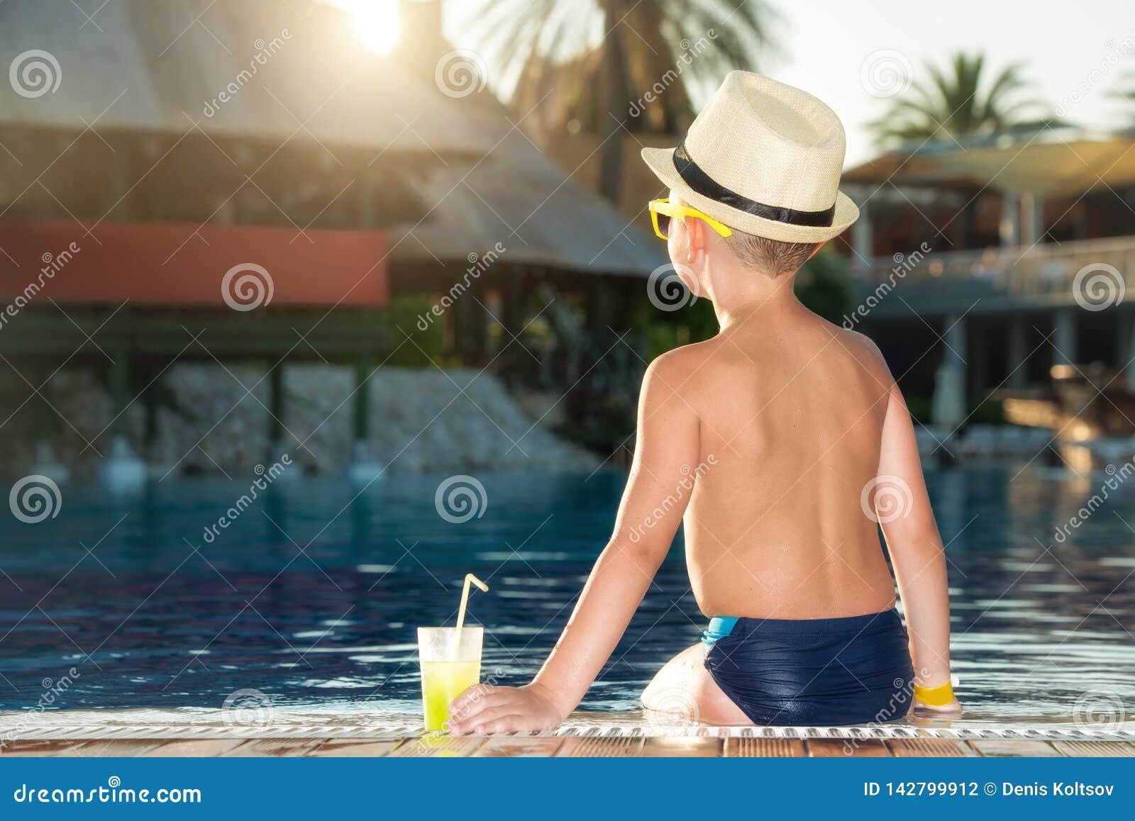 Een jongen in een strohoed met een cocktail in hand zitting op de pool