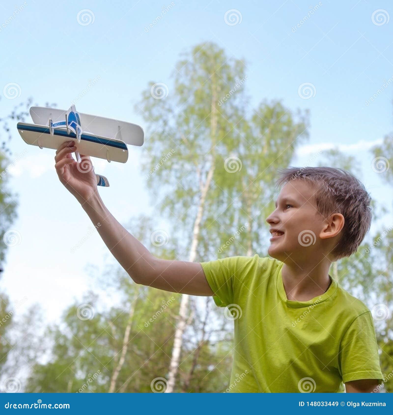 Een jongen van Europese verschijning met een vliegtuig tegen de hemel met wolken Heldere emoties Zie mijn andere werken in portef