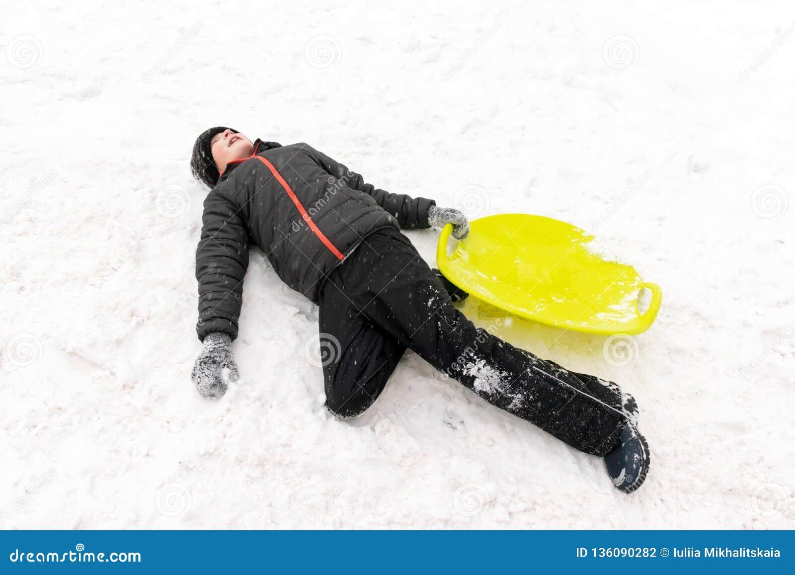 Een jongen van zeven jaar het oude liggen op de sneeuw en het houden van een groene plastic slee in zijn hand Concept de winterac