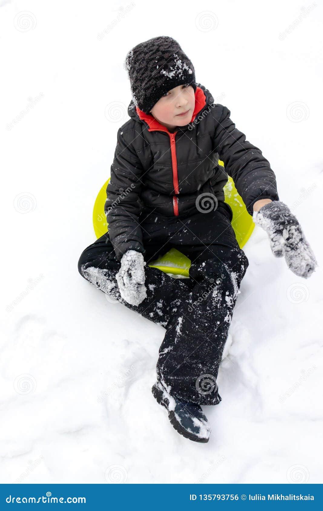 Een jongen van zeven jaar oude zittings op een groene plastic schotelslee klaar om een dia te berijden Concept de winteractivitei