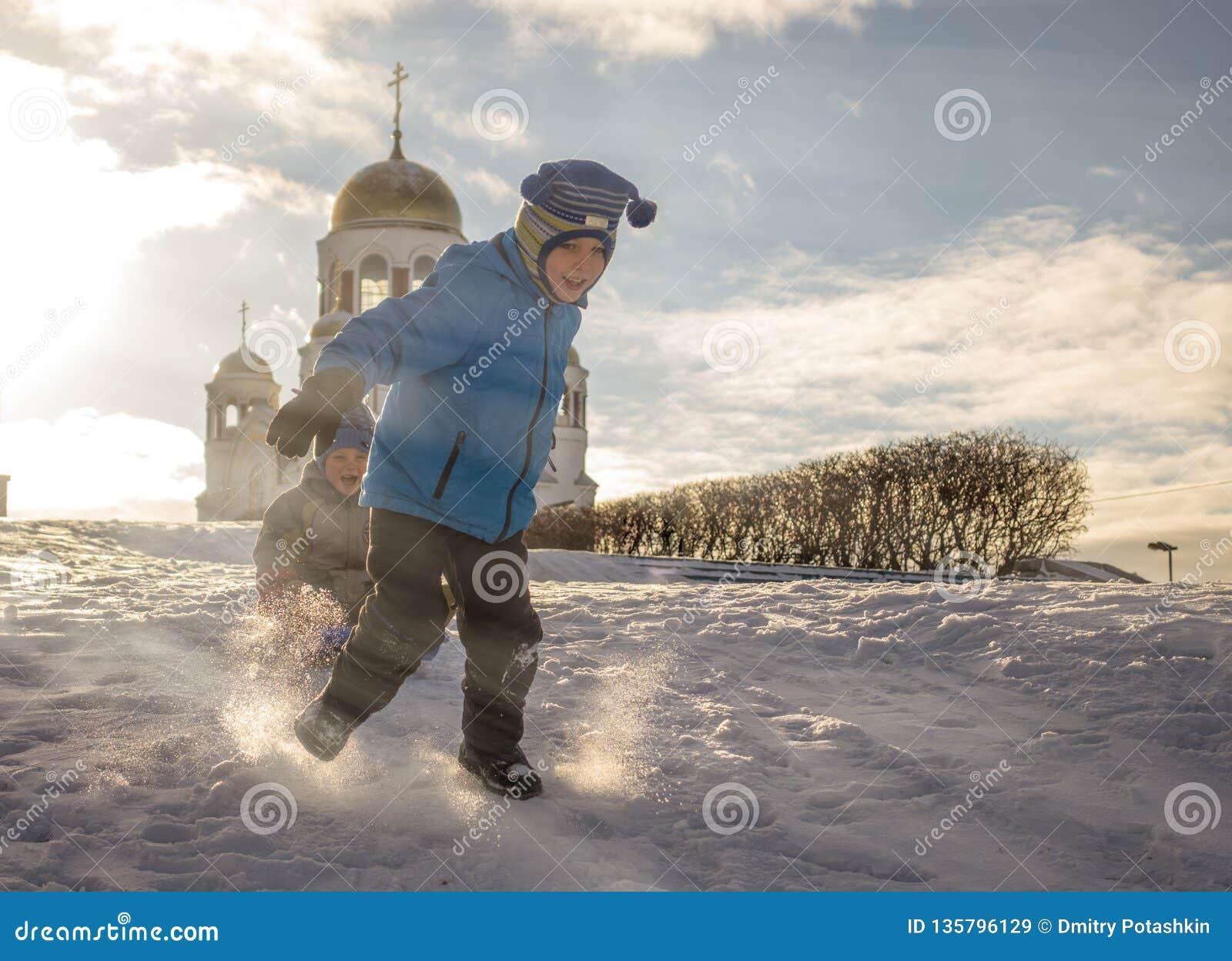 Een jongen vervoert zijn broer op een slee door zuivere sneeuw