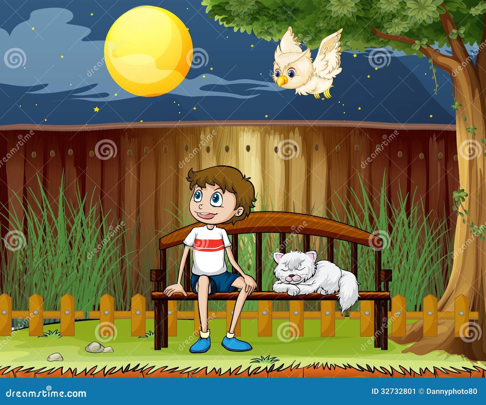 Een jongenszitting met zijn kat binnen de omheining