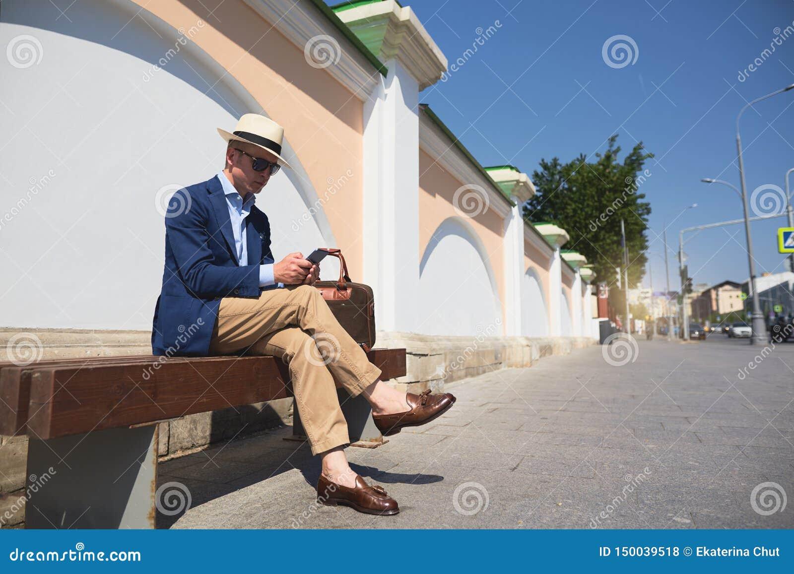 Een kerel in een pakzitting op een bank en het spreken op de telefoon