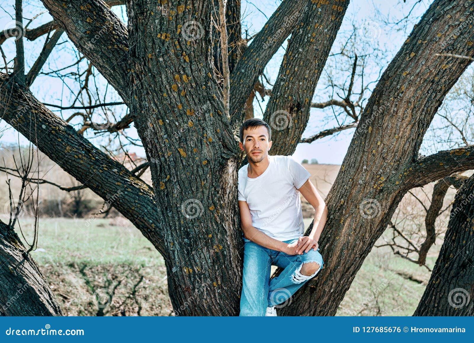 Een kerel in een witte T-shirt en jeans zit tussen de bomen