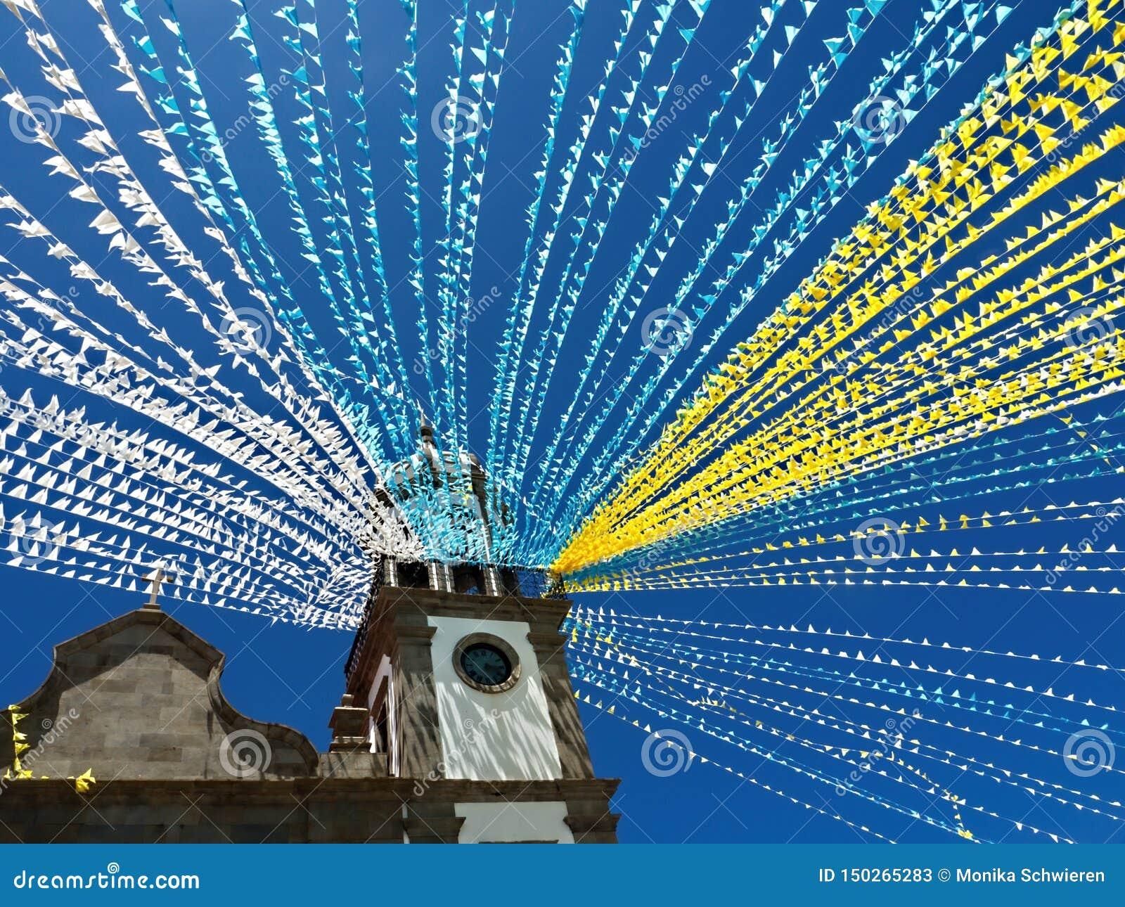 Een kerk met kleurrijke slingers wordt verfraaid die