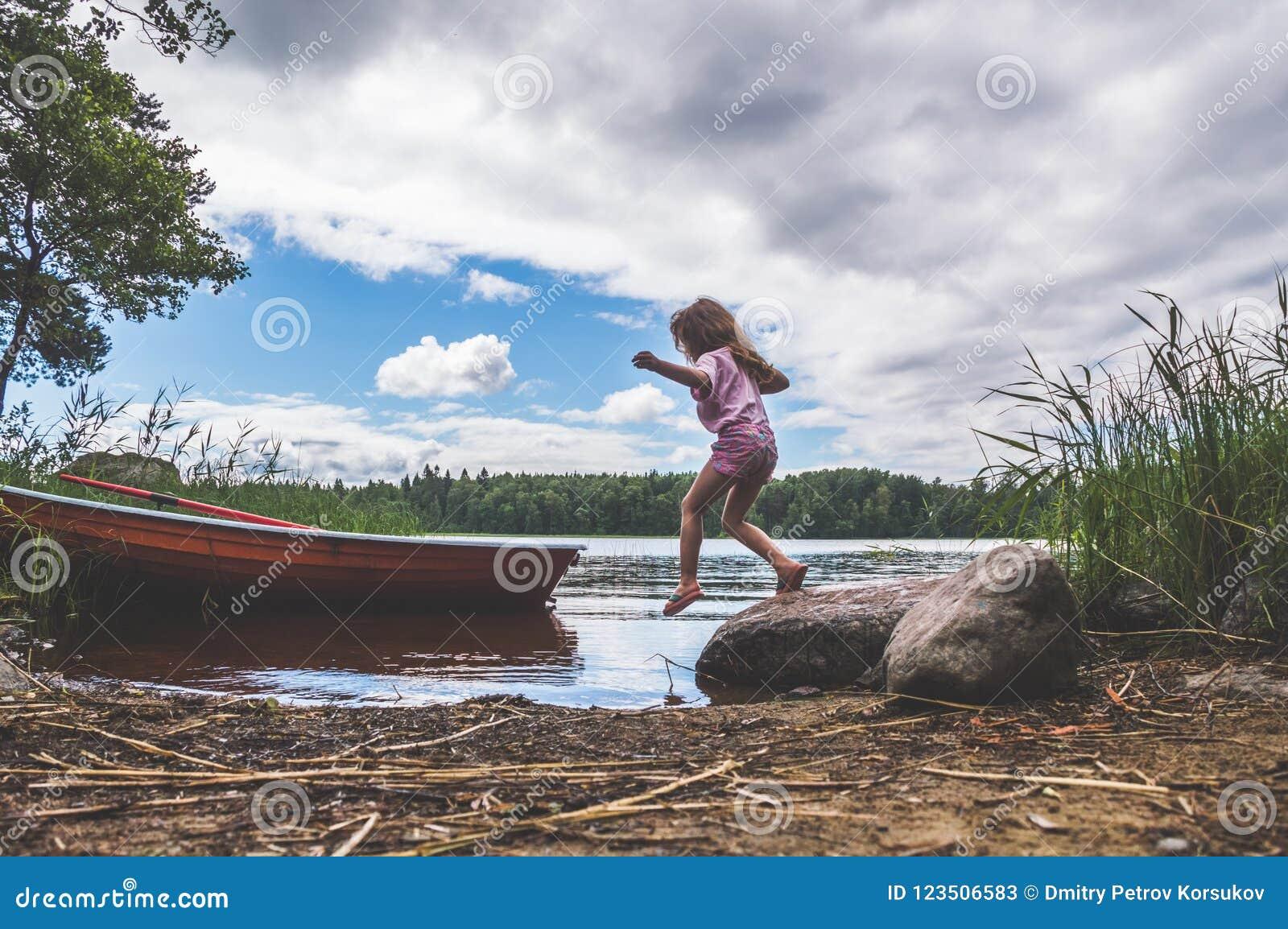 Een kind loopt op het water, meer, rivier, dichtbij de boot in w