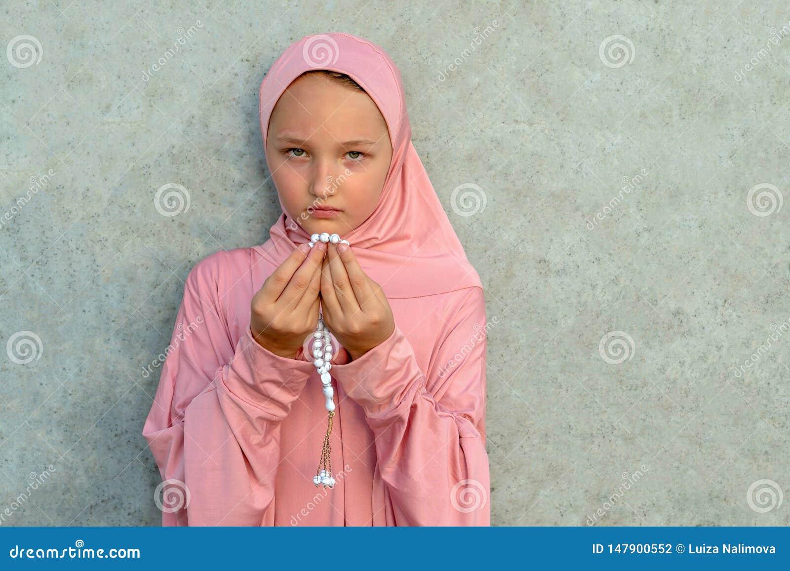 Een kind in een roze hijab met parels in zijn handen met exemplaarruimte Concept van de mensen het godsdienstige levensstijl