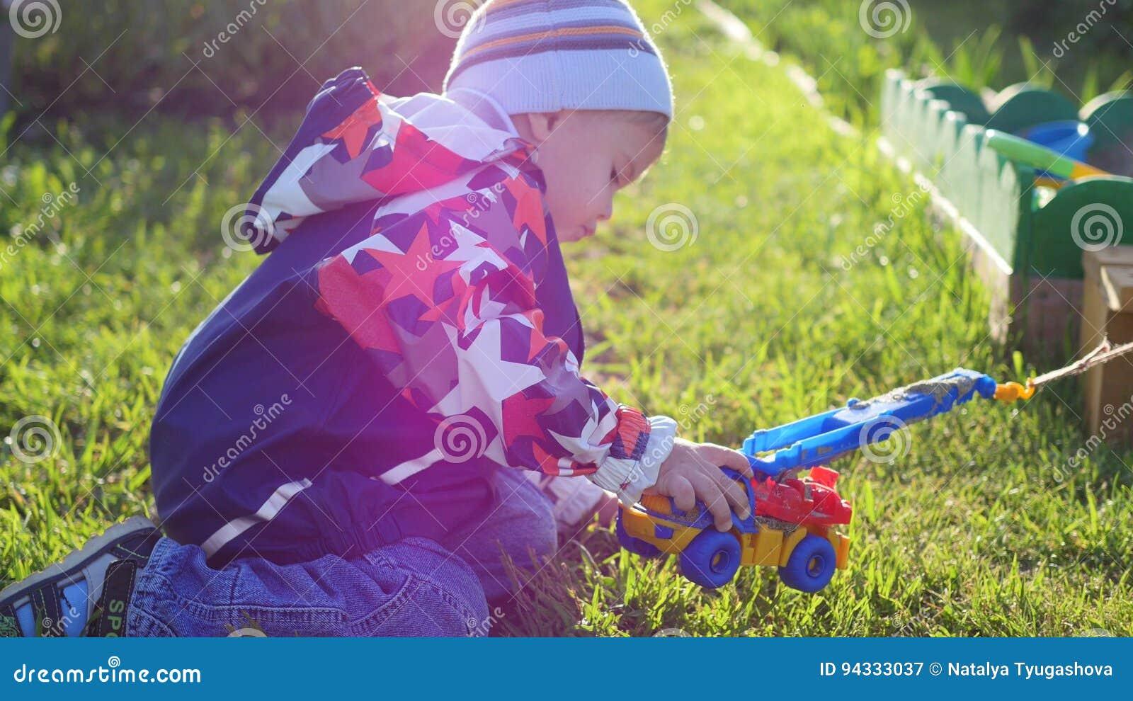 Een kind speelt met een stuk speelgoed auto op het gazon Pret en spelen in openlucht