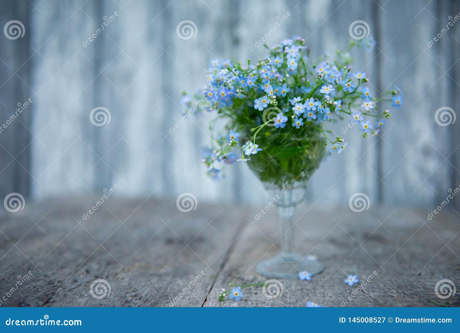 Een klein boeket van vergeet-mij-nietjes in een kristalglas op een vage achtergrond van raad schilderde met blauwe verf en een pa
