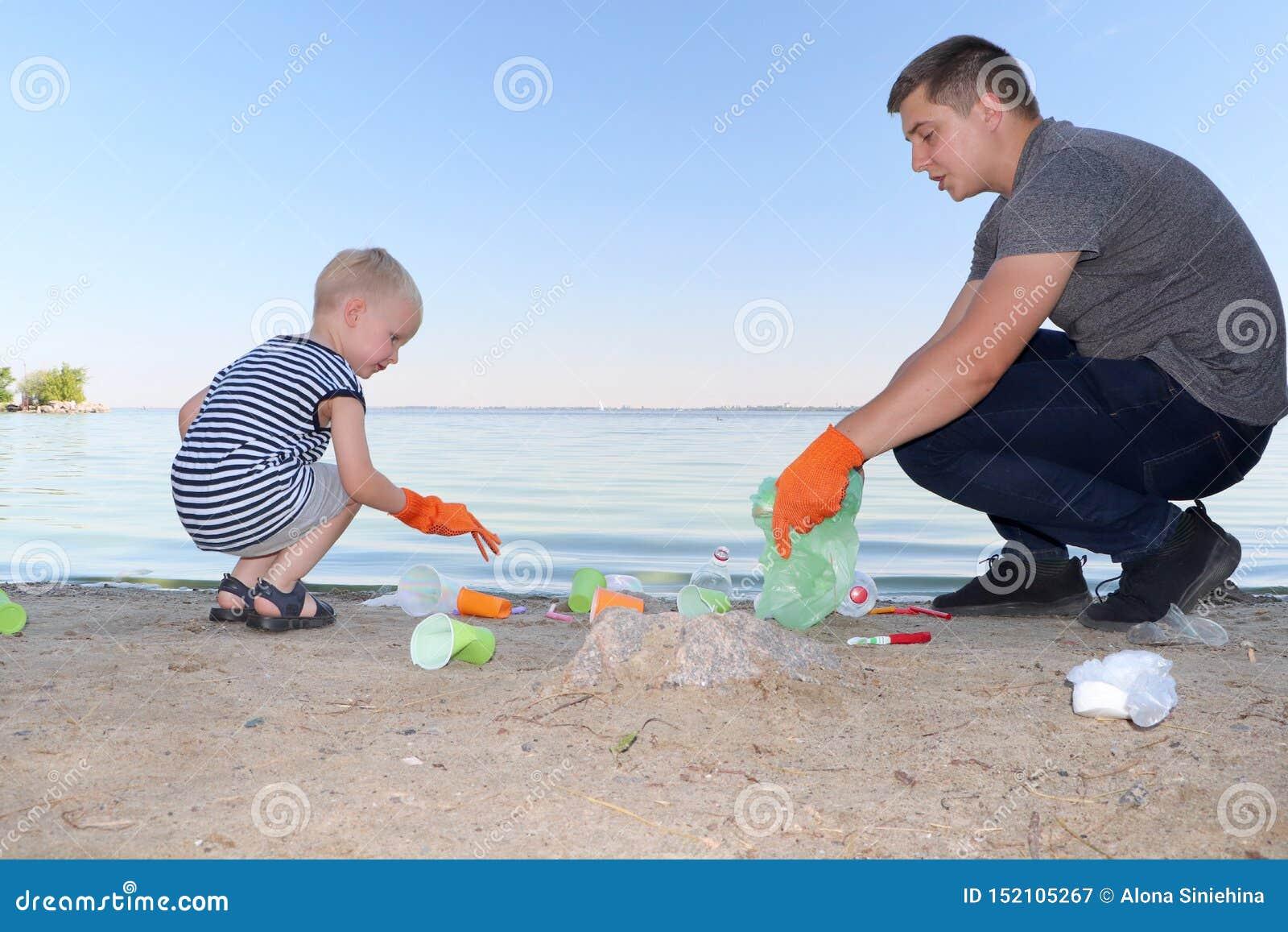 Een klein kind verzamelt afval op het strand Zijn papa richt zijn vinger waar te om huisvuil te werpen De ouders onderwijzen kind