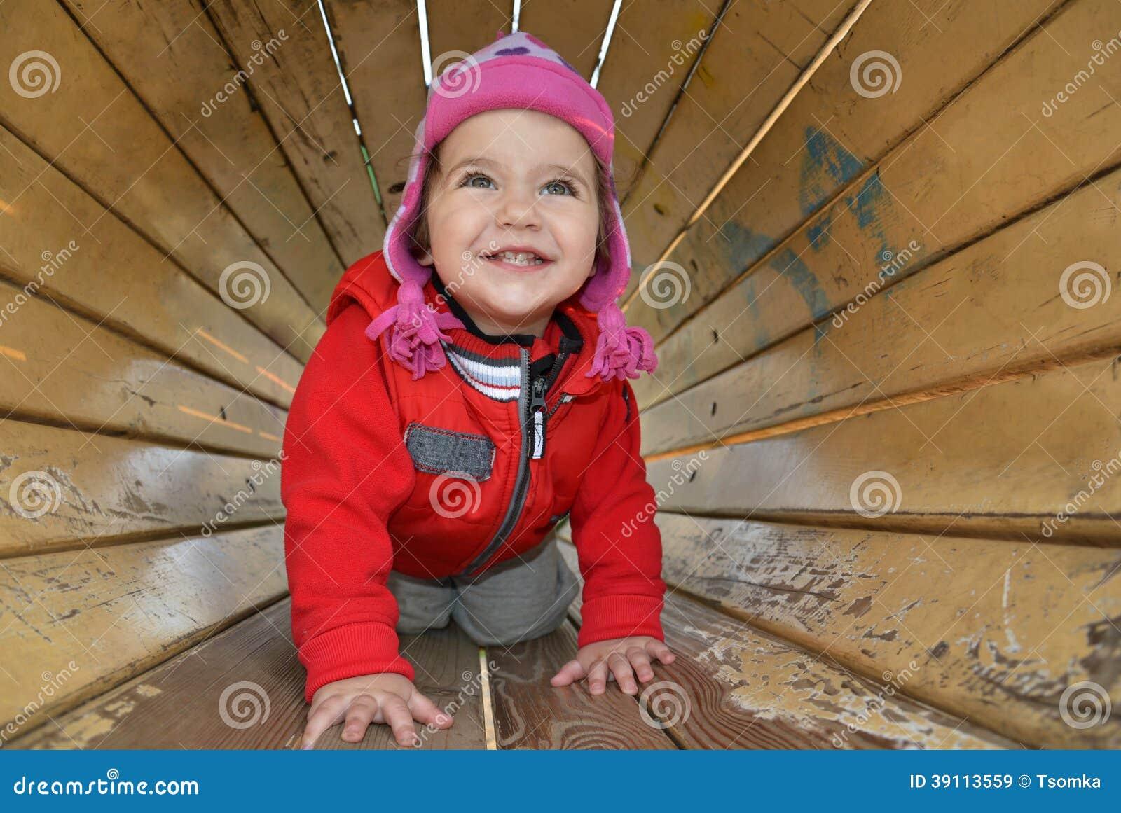 Een klein meisje die op de speelplaats spelen