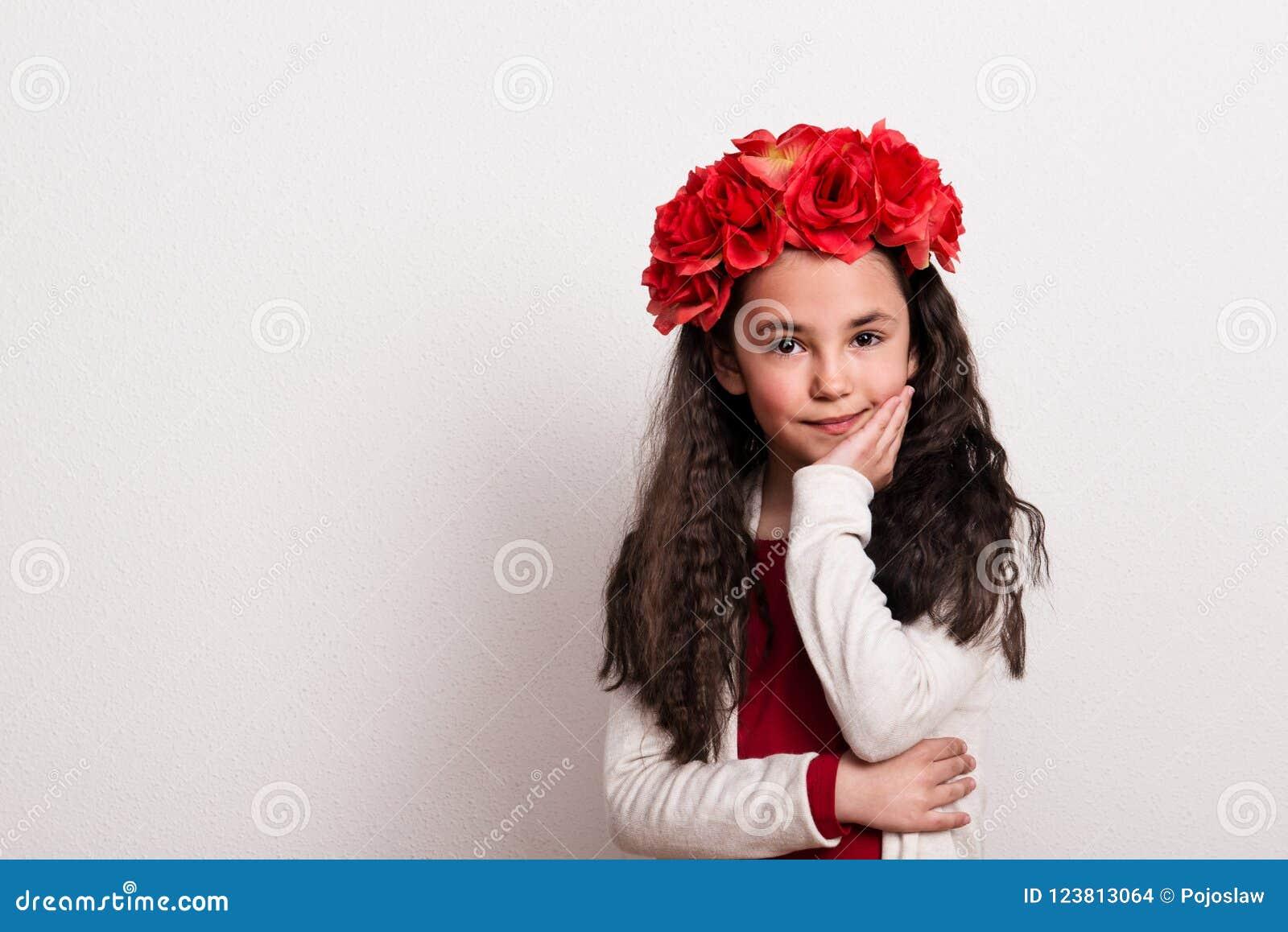 Een klein meisje met bloemhoofdband die zich in een studio, kin bevinden die op haar hand rusten