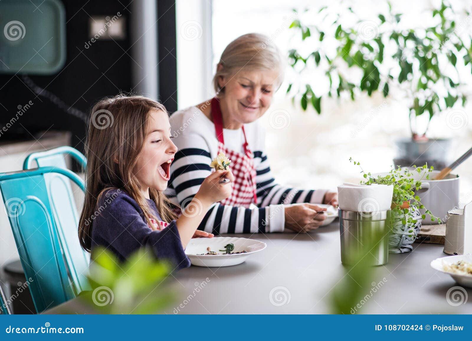 Een klein meisje met grootmoeder thuis