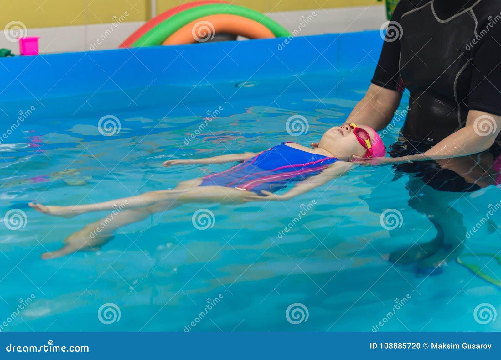 Een klein meisje van Europese verschijning in een roze rubberglb die in de pool leren te zwemmen