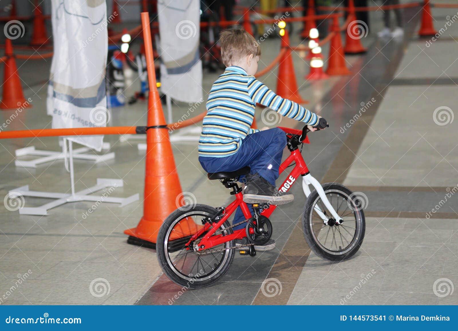 Een kleine jongen berijdt een fiets op het spoor De jongen op de fiets binnen